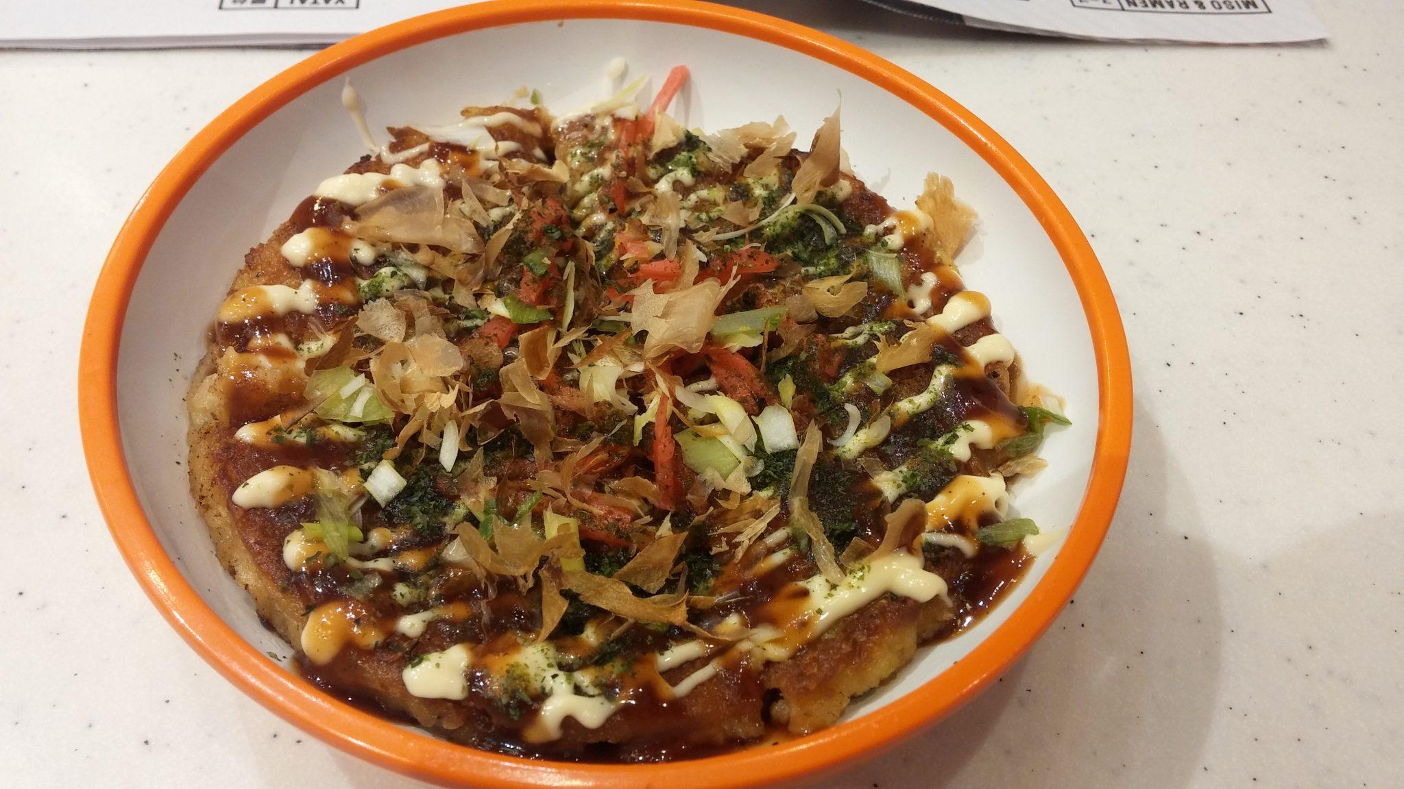 cabbage pancake topped with smoked bonito tuna flakes, katsu sauce, mayonnaise