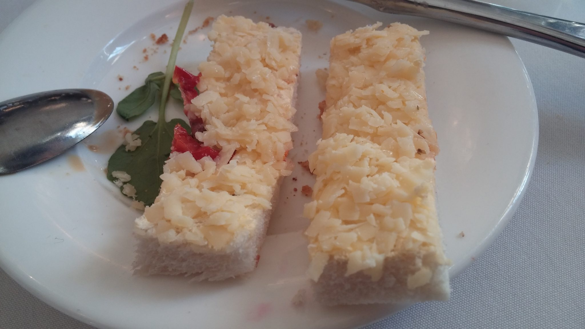 Grated cheese and bitty tomato sandwich on dry bread