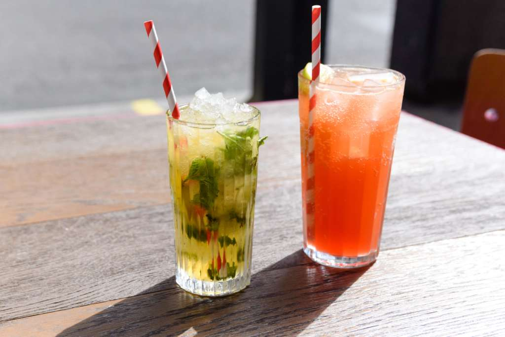 Two drinks sit on a table; the Wahaca passionfruit and hibiscus cooler, and mojito